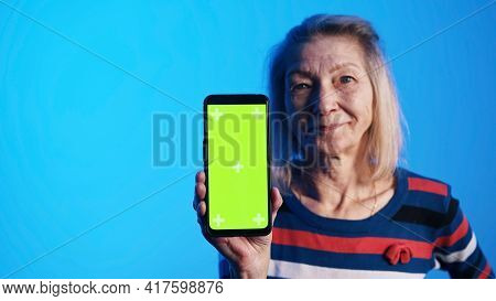 Old Caucasian Woman Showing Smartphone With Green Screen. High Quality Photo