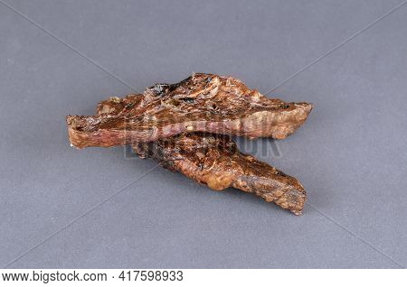 Pet Treats On A Gray Background. Two Pieces Of Dried Lungs. Natural Healthy Treats For Dogs. Close-u