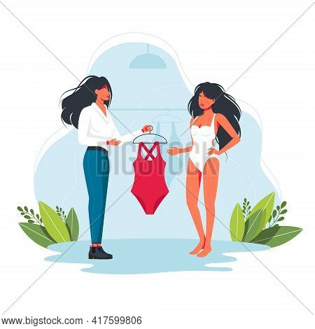 Consultant Gives A Woman To Try On A Swimsuit. Personal Stylist. Woman Tries Clothes With Fashion Co