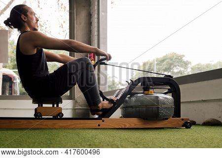 Sporty Man Training His Strength In The Gym With A Water Rowing Machine, Active And Sporty Lifestyle