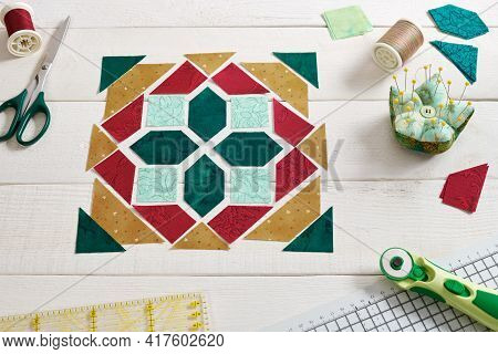 Pieces Of Fabric Laid Out In The Shape Of A Patchwork Block, Sewing And Quilting Accessories. Tradit