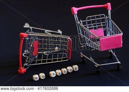Fallen Empty Metal Supermarket Trolleys And No Sales Lettering On Black Background. Deficit, Economi
