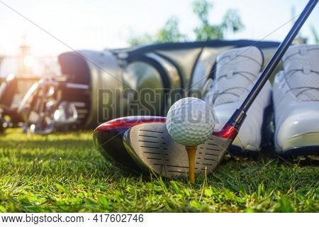 Closeup Golf Ball On Tee Ready To Be Shot. Golf Ball On Tee In The Evening Golf Course With Sunshine