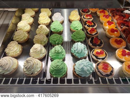 Assortment Of Sweet Delicious Cakes On The Shop Window.