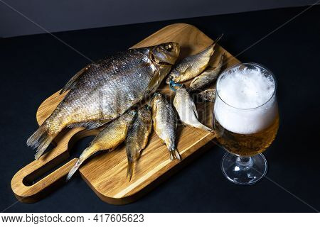 Dried Salted Roach And Bream, Delicious Clip Fish On A Wooden Background With A Glass Of Fresh Beer.