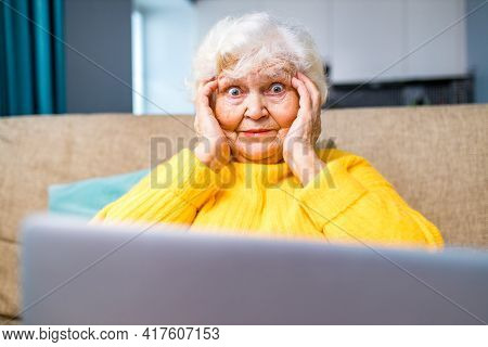 Shoked Amazed Old Woman White Gray-haired Sitting On The Sofa In Living Room With Laptop And Bills