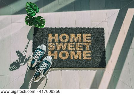 Home sweet home doormat at house entrance with sneakers. New condo homeowner moving in with plant or clean floor. Top view of house mat rug.
