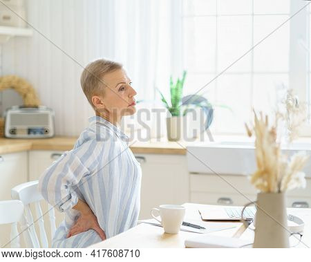 Tired Exhausted Middle Aged Business Woman Massaging Her Back While Sitting In Kitchen And Working O