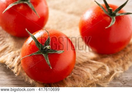 Organic Fresh Tomatoes On Rustic Wooden Table. Close Up