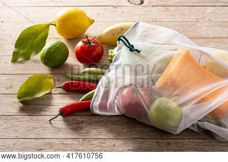Eco Friendly Reusable Shopping Bag With Vegetables And Fruit On Wooden Table