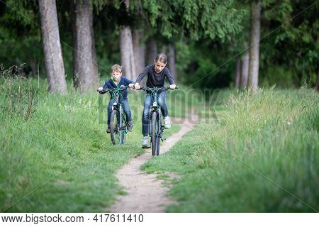Girl And Her Younger Brother Ride Bicycles In Park