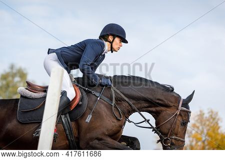 Sportswoman Jumps A Horse Over An Obstacle