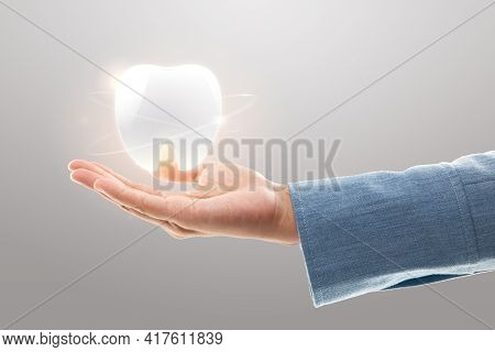 Dentist Hands Showing White Teeth Isolated On A Light Gray Background. Tooth Care And Protection Con