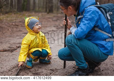 Mom And Child Walking Along The Forest Road After Rain In Raincoats, Together Draw On The Sand With