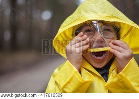 Child In A Yellow Raincoat Walking In The Forest After The Rain, Laughing And Fun, Look At Camera