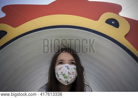 Child Girl Wearing Face Mask Comming Out Of Playground Tunnel. Hopefull Eyes For Covid-19 Crisis Con
