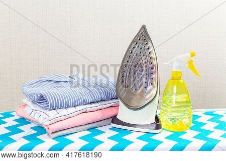 Electric Clothes Iron On The Ironing Board.