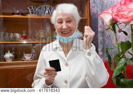 Happy Senior Woman With Face Mask Making Reservation Online From Home And Paying With Credit Card. A