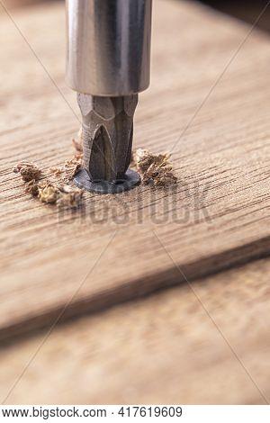Screwdriver Screw In A Wood Oaks Plank. Self-tapping Screw For Ph2 Bit. Screws Macro Photo. Construc