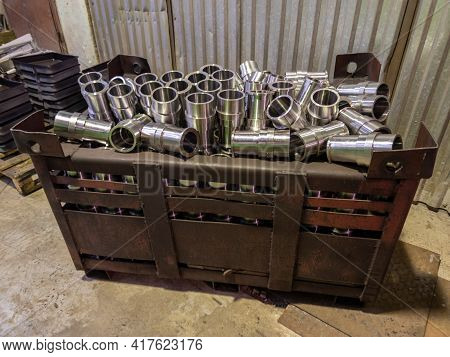 Shiny Steel Parts Overflowing Big Intermodal Steel Container Box On Factory Floor