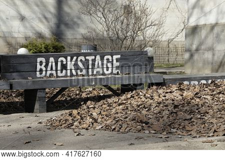 Black Bench With A White Inscription 'backstage' Next To A Large Pile Of Fallen Dry Leaves