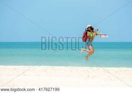 Happy Traveler And Tourism Women Travel Summer On The Beach. Asia Smiling People Jumping And Enjoy