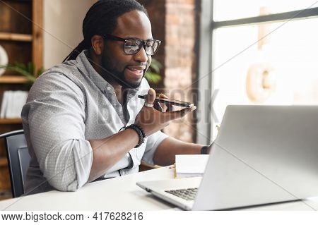 Busy African-american Businessman In Glasses With Dreadlocks Working In Office, Sitting At Desk, Hol