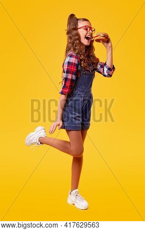 Full Body Side View Of Cheerful Teenage Girl In Denim Overall And Sneakers Biting Delicious Burger O