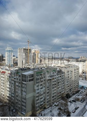 Winter In The City Of Eastern Europe. Rooftops Of Multistory Buildings And City Streets Covered With