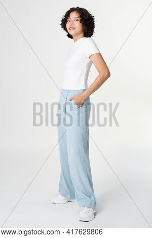 Woman in white tee and blue loose pants minimal fashion