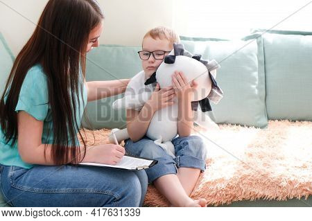 Psychologist Listens To A Small Child During A Therapy Session. A Preschool Boy Feels At Ease In The