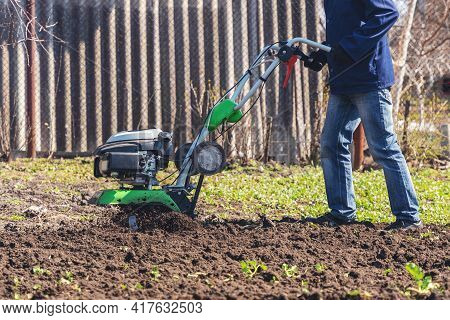 Farmer Man Plows The Land With A Cultivator Preparing The Soil For Sowing