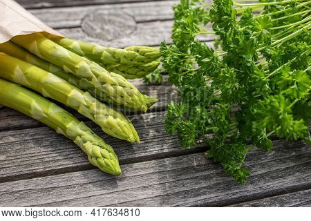 Green Asparagus And Parsley On Rustic Gray Wood. Fresh Ingredients For A Seasonal Gastronomy Backgro