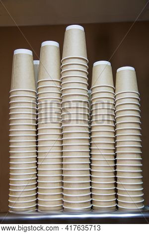 Cardboard Cups Of Gray Color Stacked In A Stack In The Form Of Skyscrapers On A Dark Brown Backgroun