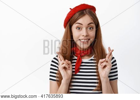 Optimistic Hopeful Girl Makes Wish, Cross Fingers For Good Luck And Looking With Happy Smile At Came