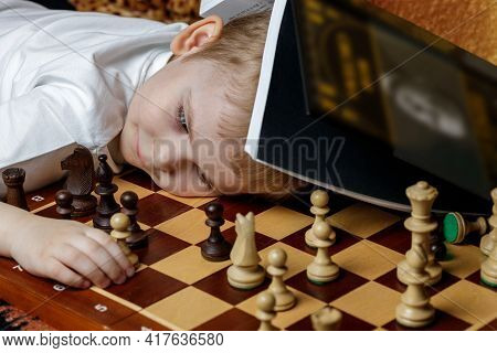 The Child Rests After Training. A Chessboard With Pieces And A Book