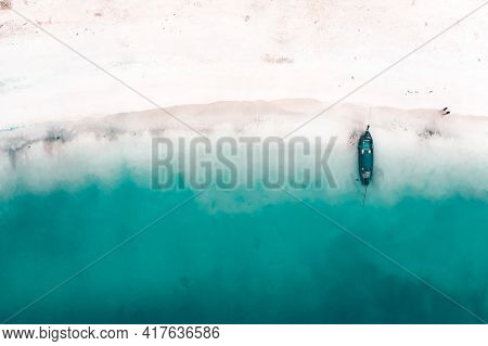 Aerial, drone view of a beautiful tropical beach with white sand, turquoise clear water and longtail boat near Krabi, Thailand.