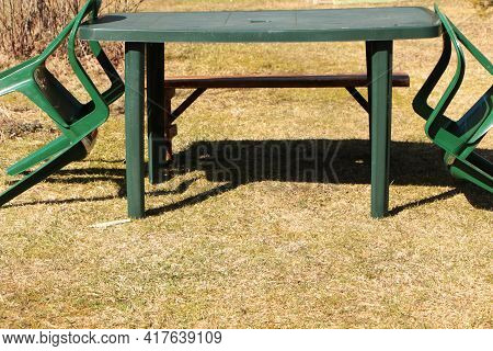 There Is A Table And Chairs For Outdoor Dining On The Green Lawn.