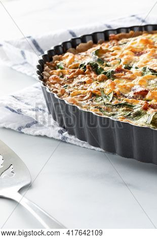 Close Up Of A Portion Of A Spinach Quiche In A Tart Pan Lit From Behind.