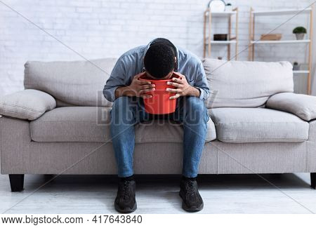 African Man Vomiting Into Bucket Sitting On Couch At Home