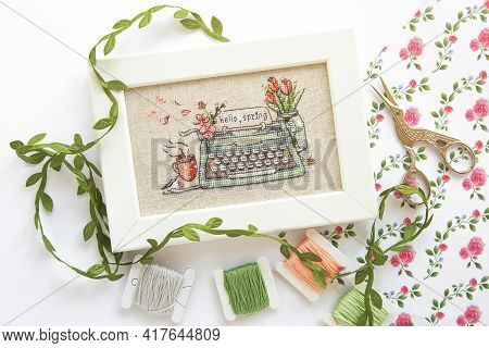 Close Up Cross Stitch Typewriter Saying Hello Spring On Linen Canvas In White Frame, Floss Threads O