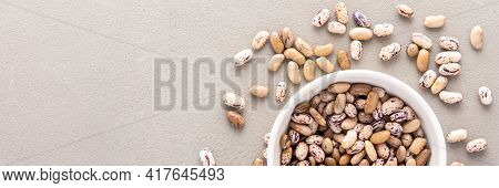 Legumes In Bowl And Scattered In The Background, Pinto Beans In A Plate Banner, Top View, Copy Space