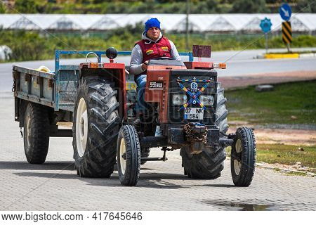 Antalya, Turkey - April 12 2021:  Young Male Worker Tractor Driver Rides His Tractor With A Trailer