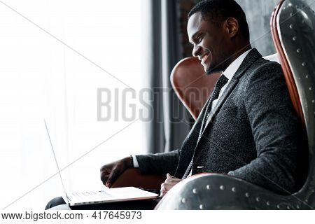 A Cheerful Dark-skinned Manager Sits On A Chair And Works At A Laptop, Smiling Broadly And Folding H