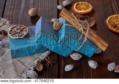 Bright, Fragrant Blue Handmade Soap, Various Spices And Nuts On The Dark Wooden Countertop.
