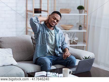 African American Man Massaging Aching Neck Sitting At Laptop Indoor