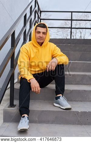 Full Length Photo Of Young Adult Dark Haired Man Dresses Casual Yellow Hoodie, Black Pants And Sneak