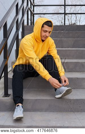 Handsome Dark Haired Male Wearing Yellow Casual Hoodie And Black Trousers, Sitting On Stairs Outdoor