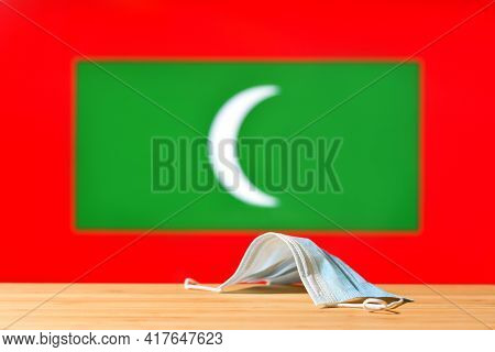 A Medical Mask Lies On The Table Against The Background Of The Flag Of Maldives. The Concept Of A Ma