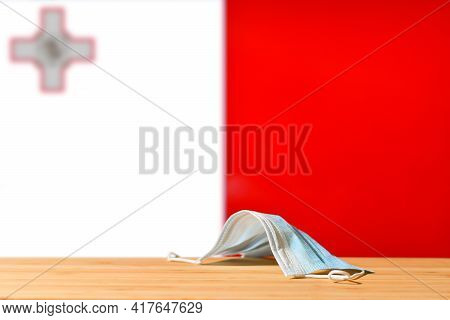 A Medical Mask Lies On The Table Against The Background Of The Flag Of Malta. The Concept Of A Manda
